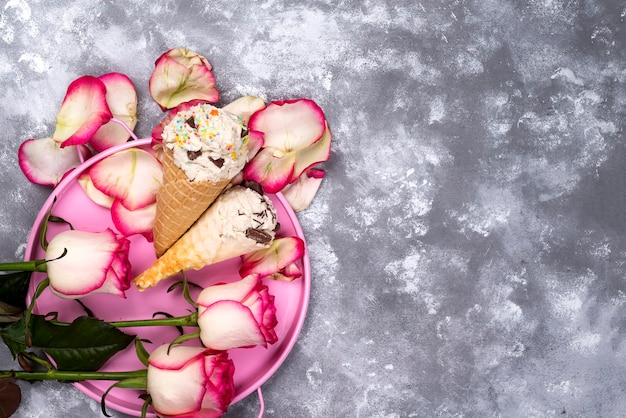 La composizione del gelato waffles con i mazzi delle rose su un fondo di pietra