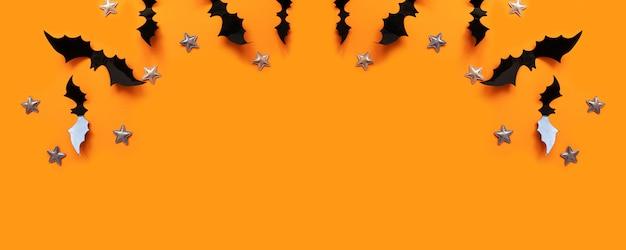 La composizione piana di disposizione di halloween dei pipistrelli di carta neri vola su e stelle d'oro