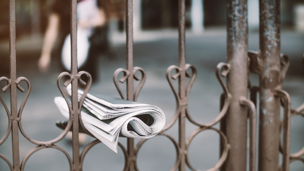 La consegna di un giornale è appesa al recinto con la donna che cammina per tenerlo.