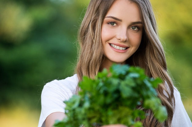 La contadina continua a coltivare ortaggi freschi. raccolto dell'azienda agricola. giovane donna che tiene un mazzo di prezzemolo.