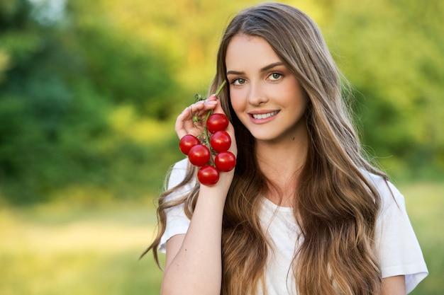 La contadina continua a coltivare ortaggi freschi. raccolto dell'azienda agricola. pomodori azienda giovane donna.