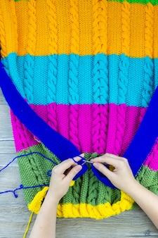 La coperta della ragazza lavora a maglia i ferri da maglia