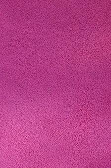 La coperta di tessuto felpato rosa furry. una trama di sfondo di materiale in pile morbido peluche rosa chiaro