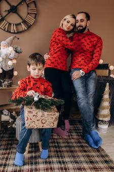 La coppia affascinante in maglioni rossi guarda il loro figlio che apre i regali prima di un albero di natale