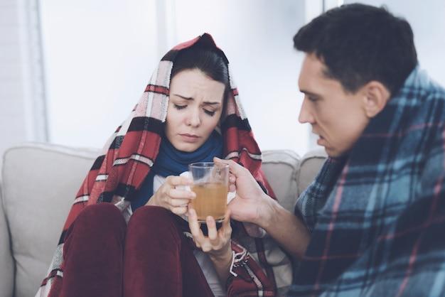 La coppia ammalata sta bevendo il tè sul sofà a casa.