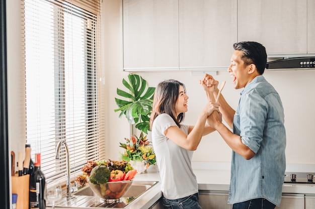 La coppia asiatica nell'amore sta cantando e ballando insieme nella cucina