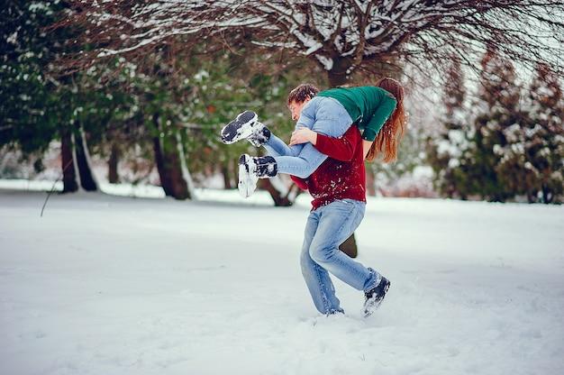 La coppia carina si diverte in un parco invernale