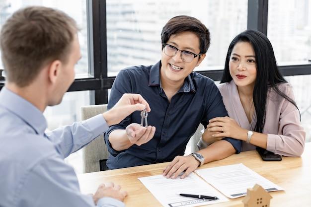 La coppia completa il contratto di acquisto di una casa e il broker fornisce la chiave di casa.