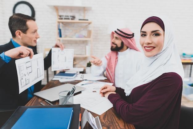 La coppia del medio oriente compra la camera all'ufficio di agente immobiliare