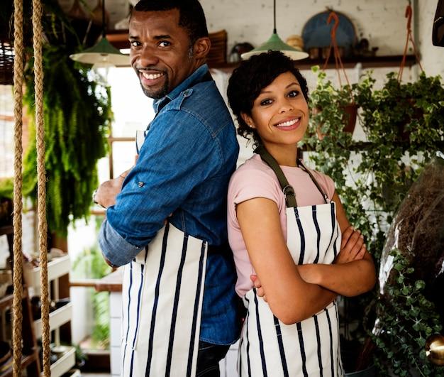 La coppia del proprietario di origine africana si leva in piedi all'interno del negozio di fiore