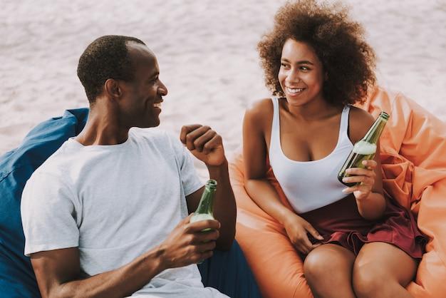 La coppia della corsa mista beve la birra fresca sulla spiaggia