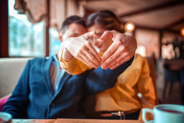 La coppia di amore fa un cuore con le mani