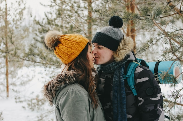 La coppia di baciare felice nell'amore al parco naturale della foresta nella stagione fredda