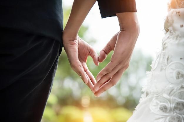 La coppia di sposi sta facendo segno della mano d'amore insieme, segno del cuore a mano
