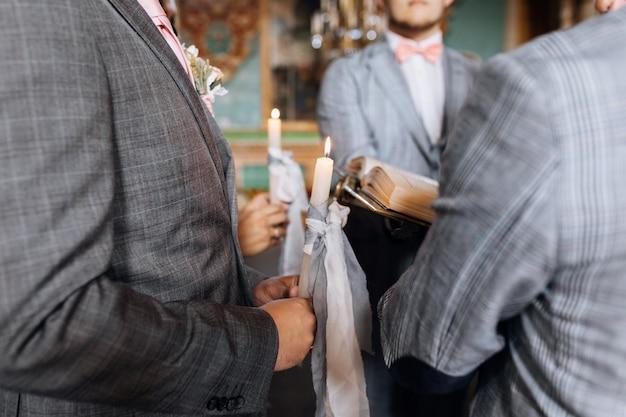 La coppia di sposi tiene in mano candele con nastri grigi durante la sacra cerimonia di matrimonio in chiesa