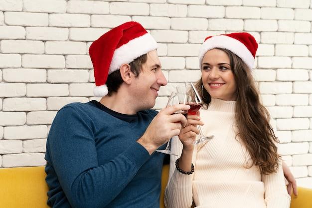La coppia è seduta a bere vino rosso sul divano.