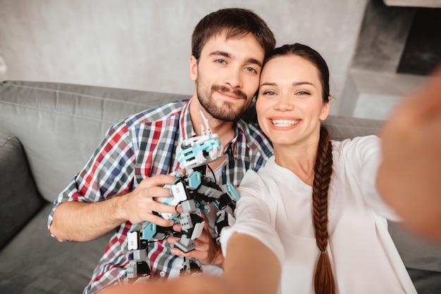 La coppia è seduta sul divano e fa selfie con un robot