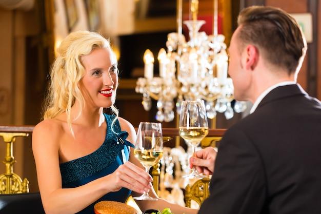 La coppia felice ha un appuntamento romantico ristorante raffinato che bevono vino e bicchieri tintinnanti, evviva, un grande lampadario