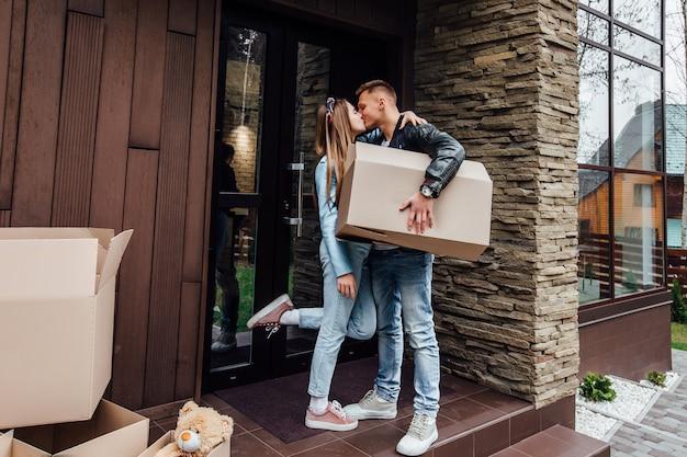 La coppia felice sta baciando con le scatole di cartone in nuova casa al giorno commovente.