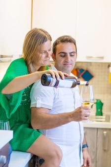 La coppia felice sta bevendo un bicchiere di vino bianco in cucina