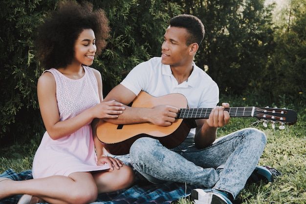 La coppia felice sta riposando nel parco all'estate