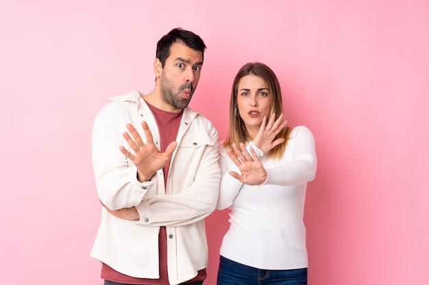La coppia nel giorno di san valentino sopra il muro rosa isolato è un po 'nervosa e spaventata allungando le mani in avanti