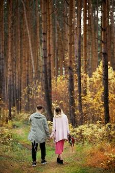 La coppia nell'amore cammina attraverso la foresta di autunno. baci e abbracci di uomini e donne, relazioni e amore. la giovane coppia sta in erba rossa gialla, un mazzo di fiori in mano della donna