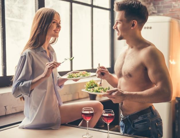 La coppia parla e sorride mentre fa una cena romantica