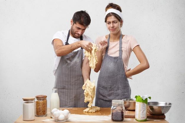 La coppia perplessa guarda la pasta fatta male, ha una giornata infruttuosa, fatta con ricetta sbagliata