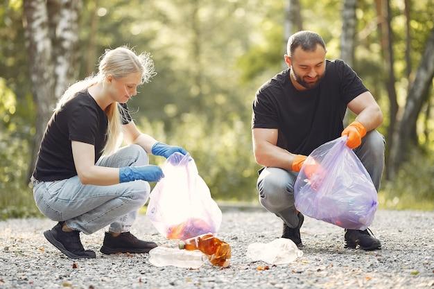 La coppia raccoglie l'immondizia nei sacchetti di immondizia in parco
