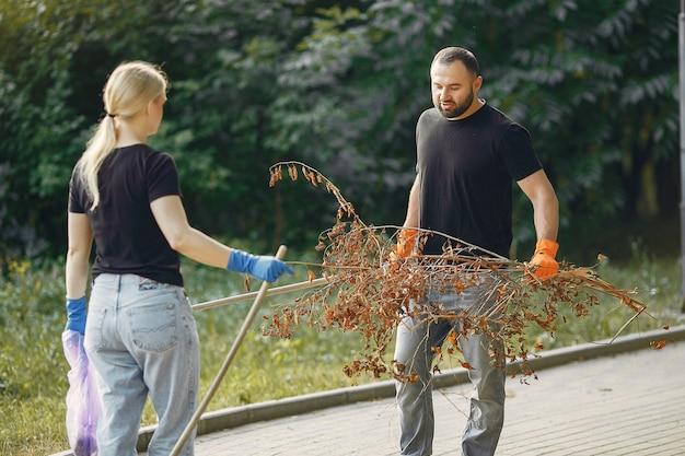 La coppia raccoglie le foglie e pulisce il parco