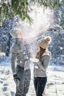 La coppia scuote il ramo dell'abete con neve. le persone si divertono
