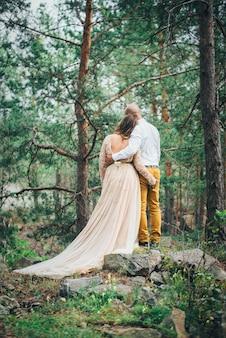 La coppia si abbraccia e sta guardando la natura nella foresta
