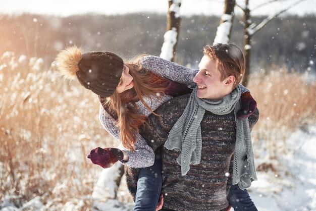 La coppia si diverte e ride. bacio. giovani coppie dei pantaloni a vita bassa che si abbracciano nel parco di inverno. storia d'amore invernale, una bellissima giovane coppia elegante. moda invernale con fidanzato e fidanzata