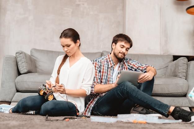La coppia si siede sul pavimento. lavora insieme con robotica.