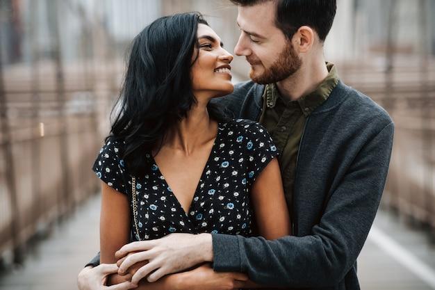 La coppia splendida dell'uomo americano con la barba e la donna orientale tenera si abbracciano
