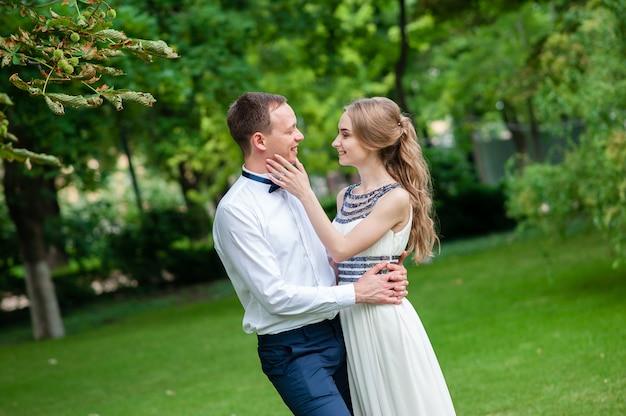 La coppia sposata sta camminando e abbracciando nel parco.