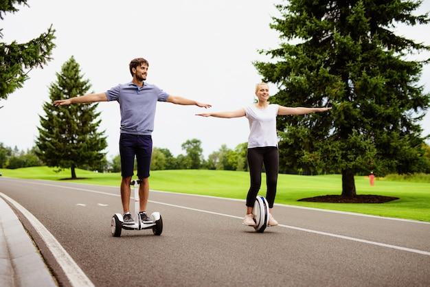 La coppia sta cavalcando una giroscopio e un monocolo nel parco.