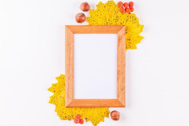 La cornice della foto di stile di autunno con copyspace ha circondato le foglie gialle, bacche di sorbo