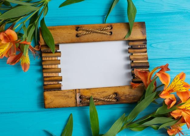 La cornice di legno della foto su legno blu con i fiori di alstroemeria copia lo spazio