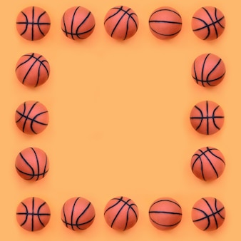 La cornice di tante piccole palline arancioni per il gioco sportivo di pallacanestro si trova su carta color arancione pastello onfashion in un concetto minimale