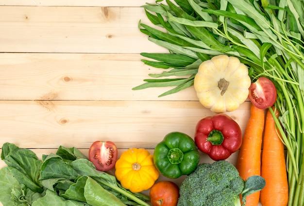 La cornice di verdure intorno con i pomodori, i peperoni, le carote, la lattuga di zucca e la verdura verde