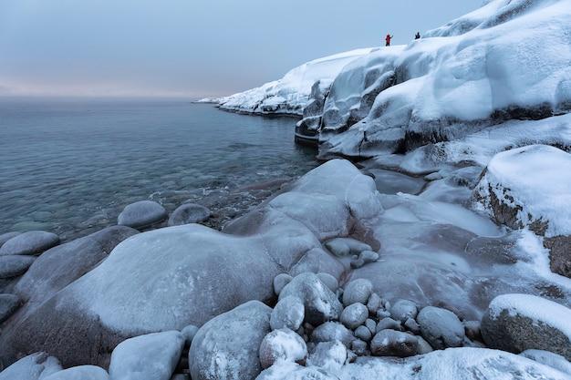 La costa del mare di barents e le montagne coperte di neve. un viaggio a teriberka, penisola di kola. regione polare russa