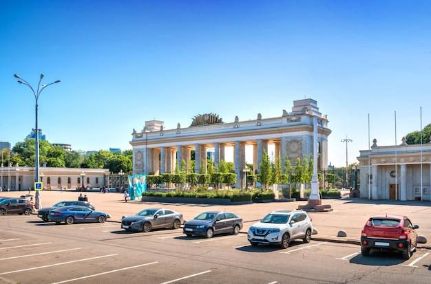 La costruzione dell'ingresso al gorkij park a mosca e le auto nel parcheggio sotto un cielo azzurro estivo