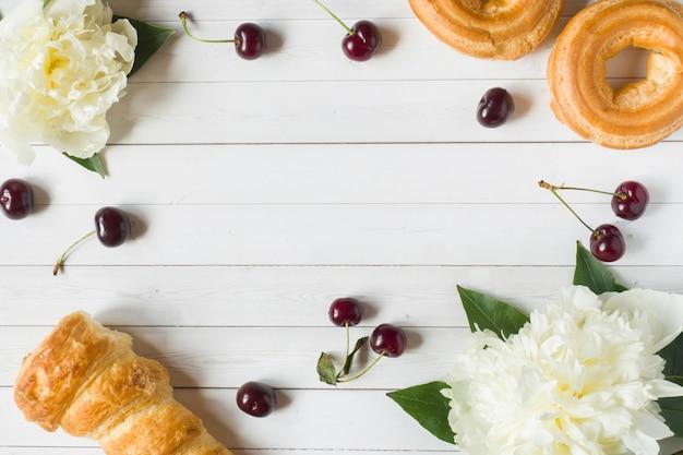 La crema della pagina agglutina i fiori della ciliegia della peonia. copia spazio piatto lay