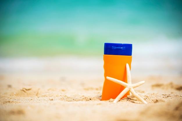 La crema solare protegge la pelle delle donne sulla spiaggia all'aperto estiva tropicale.