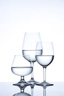 La cristalleria e la bottiglia hanno riempito di acqua su bianco
