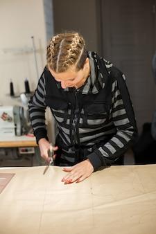 La cucitrice bionda della donna taglia dal modello della carta del mestiere per la fabbricazione dei vestiti