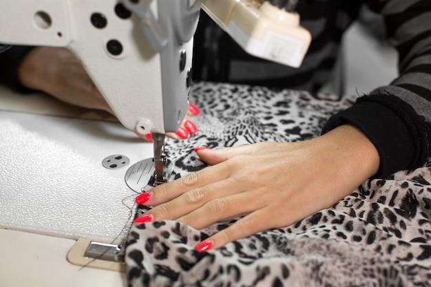 La cucitrice del primo piano cuce a mano il tessuto sulla macchina per cucire