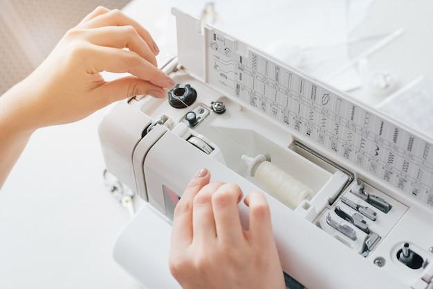 La cucitrice regola la macchina per cucire per funzionare